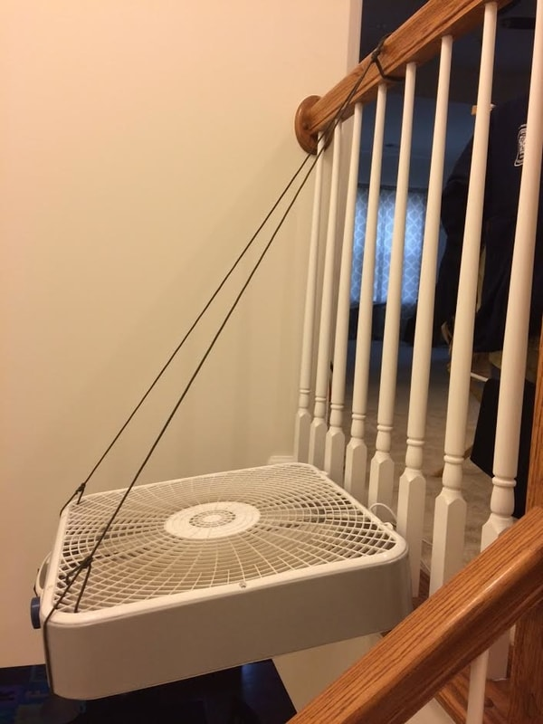 fan hung in stairway with paracord